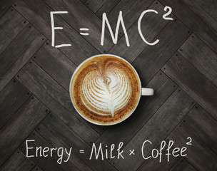 The cup of black energy coffee with milk and two funny formulas. Wooden background.
