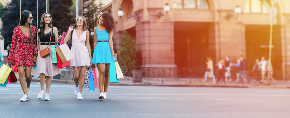 Crossing roads. Full-length photo of four beautiful women walking along the city street in sophisticated dresses and carrying shopping bags, laughing and chatting to each other.