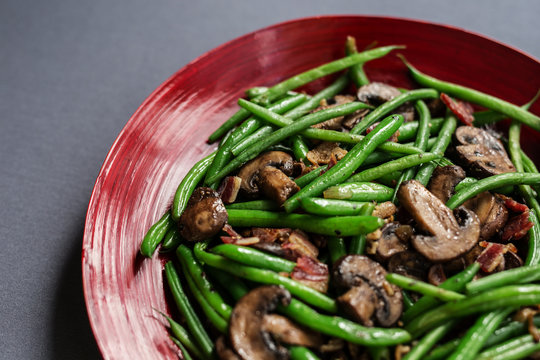 Green beans with mushrooms and bacon. Shown in red bamboo bowl, overhead view on gray background. Copy space.