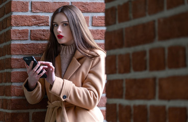 portrait of a girl on the street with phone in hands. she's writing a secret text. a young woman sits against a brick wall and talks on the phone. on young girl autumn beige overcoat. the concept of