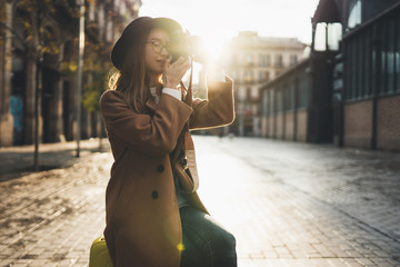 Tourist Girl in hat travels in Barcelona holiday. Photographer in glasses take photo on retro camera. Sunlight flare street in europe city. Traveler hipster shooting architecture, copy space mockup