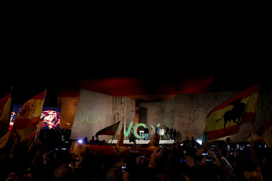 Members of Spain's far-right party VOX Ivan Espinosa, Javier Ortega Smith, Santiago Abascal and Rocio Monasterio listen to Spain's national anthem as a big Spanish flag is displayed in the background at the end of the campaign closing rally ahead of the ge