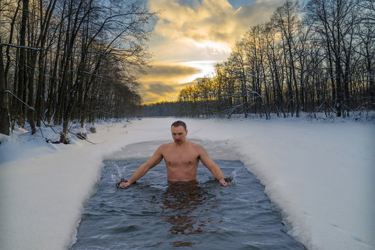 Winter swimming in cold water. Ice hole in the forest, extreme hardening of the body