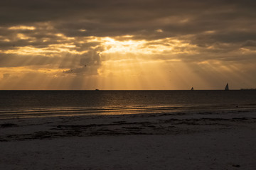 Sailboats on the horizon as the sun peeks through clouds with beams of light during sunset on Fort Myers Beach