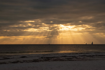 Sailboats on the horizon as the sun peeks through clouds with beams of light during sunset
