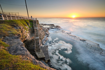 The Bogey Hole at sunrise with waves crashing into ocean bath, Newcastle, NSW, Australia