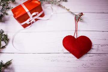 A heart hanging from a spruce branch on a white wooden table. A Christmas present wrapped in red paper and white ribbon besides.  Flat lay with copy space.