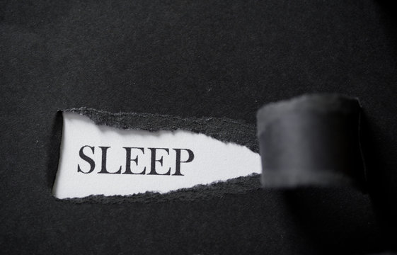 Word SLEEP printed on a white background with black torn paper.