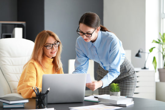 Mature businesswoman and her assistant working in office