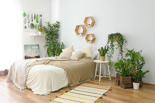 Stylish interior of bedroom with green houseplants