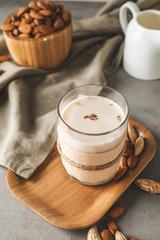 Glass of almond milk on grey background