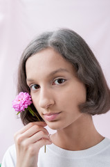 Portrait of a brown-Eyed girl on a pink background, holding a flower of lilac chrysanthemum