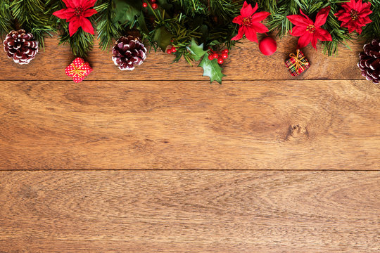 Christmas background with pine branches, red flowers, and cones on wooden board with copy space. Top view