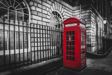 Traditional and iconic old red telephone box in London UK, isolated by color saturation.