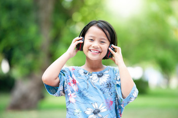 Asian cute Girl with Headphones Listen Music While Relaxing in the Park. Funny little girl with headphones on nature.