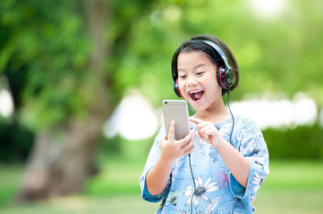 Asian cute girl in park on sunny day of spring or summer, with smart phone and headphones, select or texting and big smiling with copy space.