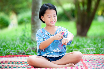 Spraying insect repellent on skin outdoor. Mosquito repellent spray. little asian girls spraying insect repellent against bug bites on arm skin outdoor in nature forest using spray bottle.
