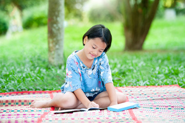 Beautiful asian little girl draws a picture in the park using a color pencil with paints and drawing note book. Learning and drawing in green park,Portrait of happy little girls child with smiling.