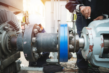 Technician inspector alignment pump  and electric motor, Repairing work in factory concept Fotomurales