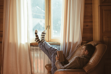 Young man in warm sweater reading by the window inside cozy log cabin