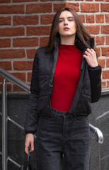 a young woman poses in black jeans and a black autumn jacket. she is also wearing a red sweater. She's standing outside the building. Autumn clothes on the model
