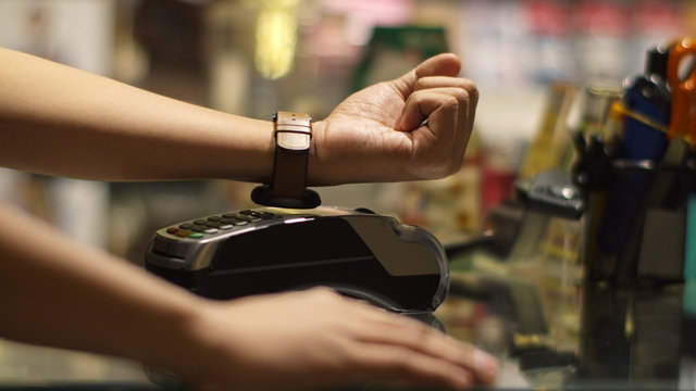 Young man using smart watch contactless payment in shop