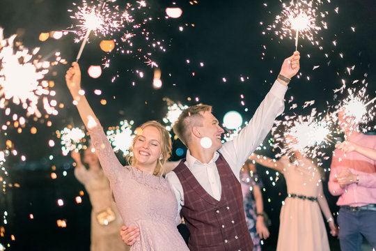 Beautiful wedding finale, the bride and groom and their guests lit sparklers in the street