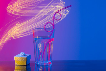 Glass with beverage, curly straw, gift in neon pink and blue light on mirror bar, yellow light...