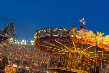 Antique merry-go--round on Red Square fair during popular New Year and Christmas festivities with GUM building on background, Moscow, Russia