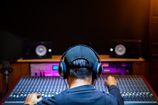 back of asian male professional music producer, sound engineer mixing a song on audio mixing console in recording studio. music production, post production concept