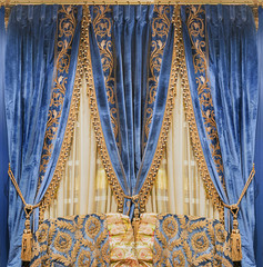 Luxurious blue velvet curtains, embroidered with gold ornaments and fringe