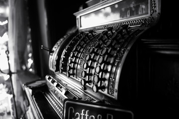 Black and white image of an old 19th century cash register. Selective focus on cashier buttons.