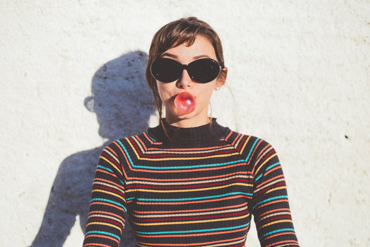 Portrait of young woman in vintage sunglasses with bubble gum