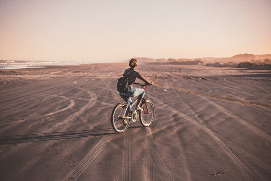 woman on a bike at the beach during sunset