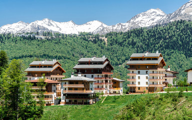 Wall Mural - Hotel on a background of beautiful mountains. Family outdoor activities. A resort town in the mountains of the Caucasus.