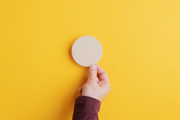 Male hand placing blank wooden cut circle on yellow background