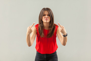 Portrait of crazy angry brunette young woman in red shirt standing with middle finger fuck sign and looking at camera with anger face. indoor, studio shot, isolated on gray background.