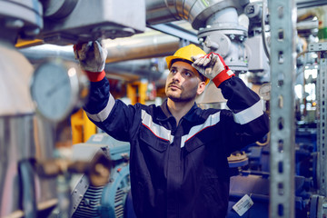 Handsome Caucasian blue collar worker in protective uniform and with hardhat on head checking on boiler while standing in factory.