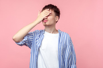 Facepalm. Portrait of distressed brown-haired man in casual striped shirt standing with hand on head, feeling regret and desperation, forgetful, bad memory. indoor studio shot, pink background