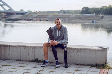 Fotomurales - Handsome sporty caucasian handicapped man in sportswear and with artificial leg sitting on quay and holding another artificial leg.