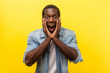 Oh my god, wow! Portrait of stunned shocked man in denim shirt holding hands on face and looking with big amazed eyes, surprised by unbelievable news. indoor studio shot isolated on yellow background Fotobehang