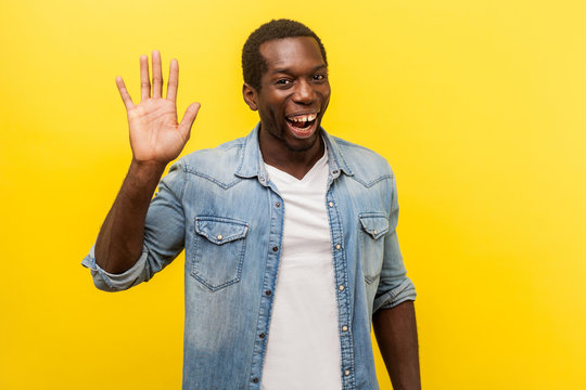 Hello! Portrait of positive handsome man in denim casual shirt with rolled up sleeves smiling friendly and waving hand saying hi, welcoming gesture. indoor studio shot isolated on yellow background