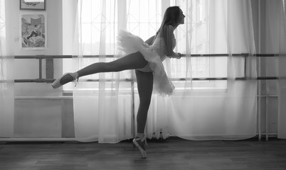 Young ballet dancer on a warm-up. The ballerina is preparing to perform in the studio. A girl in...