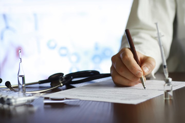 A man signs a medical document. Medical equipment on the table. Stethoscope and ampoules with...