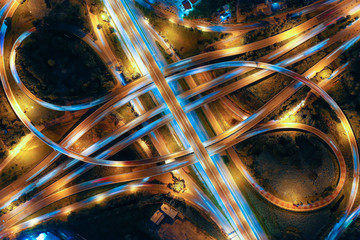 Aerial view of Smart transportation with Expressway, Road and Roundabout, busy highway traffic night time. Important infrastructure.