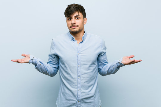 Young hispanic business man doubting and shrugging shoulders in questioning gesture.