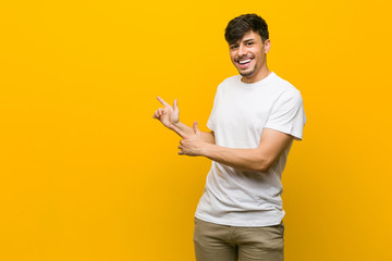 Young hispanic casual man pointing with forefingers to a copy space, expressing excitement and desire.