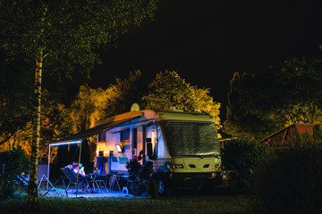 People sit under an awning and watch TV, Night view of the parking lot for a motorhome, camper van, campsite camp for sleeping and relaxing. vacation and travel tour. motorcycle.