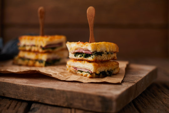 Baked spinach and ham sandwich with sauce.