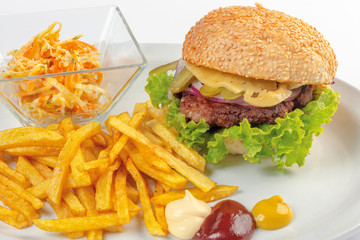 fast food menu. hamburger, french fries and salad. burger with beef stake, cheese onion and pickle. mayonnaise ketchup mustard on the white plate. healthy variation of junk food. close up view